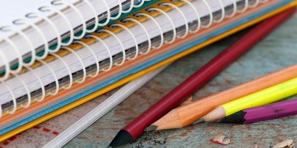Pencils laying next to wire notebooks